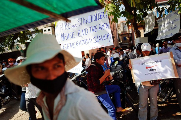 Garment workers hold signs during a gathering of workers from Sabrina (Cambodia) Garment Manufacturing Corp, which produces clothing for U.S. sportswear company Nike, at their union headquarters in Phnom Penh