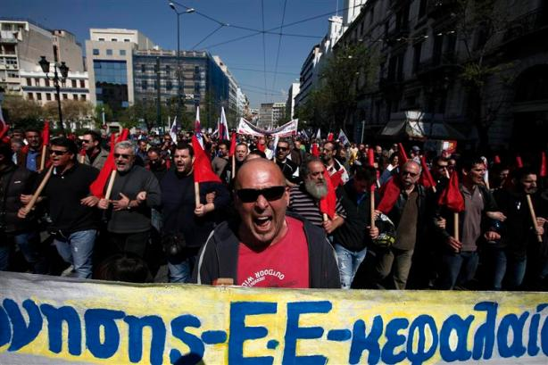 Protesters from the Communist-affiliated trade union PAME shout slogans as they march towards the parliament during a general labour strike in Athens