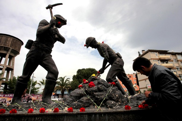 A man lays carnations at the Miners Monument in central Soma, a district in Turkey's western province of Manisa